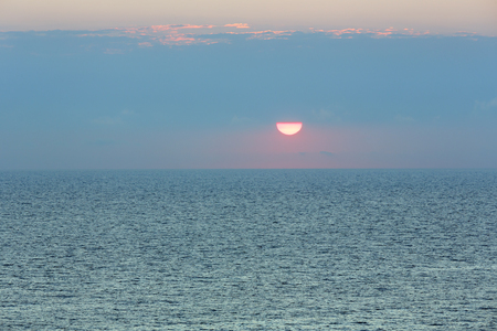 fascinate: Sunrise sea scenery and sun with red edging in sky.
