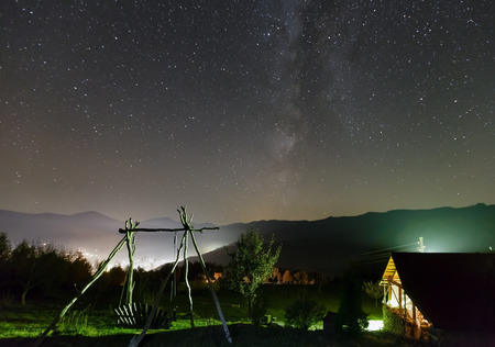 starlit sky: Milky Way in starry night sky and rural yard illuminated in green color on mountain hill. Stock Photo