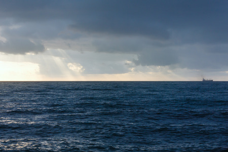 breaking through: Seascape and sunbeams breaking through gray clouds