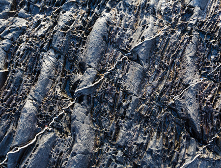 stratified: Part of rock closeup with white stripes of another geological material.