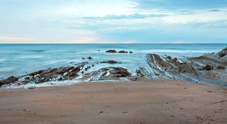stratified: Twilight ocean coast with ribbed stratiform rock formations (Atlantic Ocean, Spain).