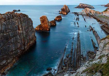 stratified: Atlantic ocean rocky coastline near Portio Beach (Pielagos, Cantabria, Spain) evening view.