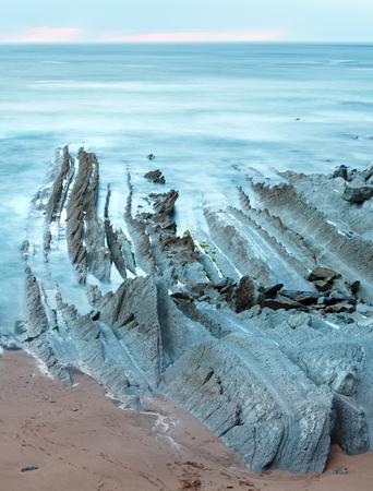 stratified: Twilight ocean coast with ribbed stratiform rock formations. (Atlantic Ocean, Spain). Stock Photo