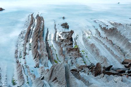ribbed: Twilight ocean coast with ribbed stratiform rock formations. (Atlantic Ocean, Spain). Stock Photo