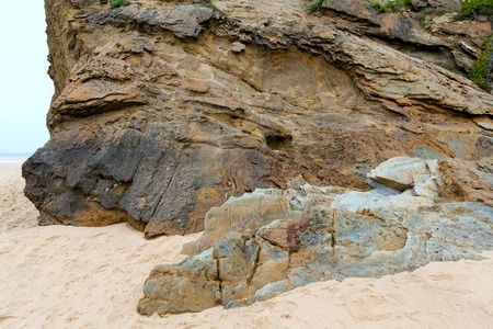 stratified: Stratiform rock on sandy beach and sea behind. Stock Photo