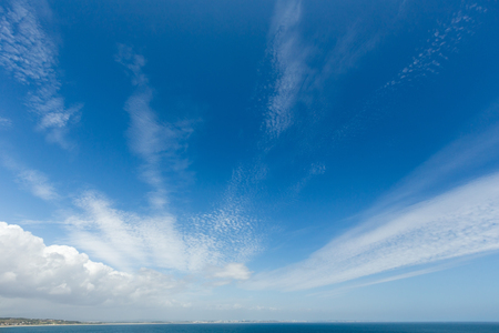 Blue sky with white clouds (background) over sea.