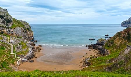 bajando escaleras: Spring sea rocky coast with stone stairway going down to sandy beach (San Julian Beach, Liendo, Cantabria, Spain).