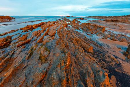 gloaming: Twilight ocean coast with ribbed stratiform rock formations (Atlantic Ocean, Cantabria, Spain).