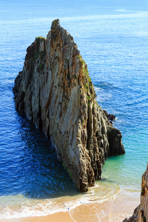 Sandy Mexota beach and pointed rock (Spain). Atlantic Ocean coastline landscape.