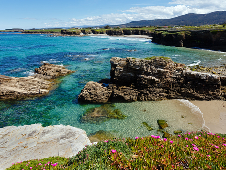 beaches of spain: Summer blossoming Atlantic coastline landscape with pink flowers and three beaches (Spain).