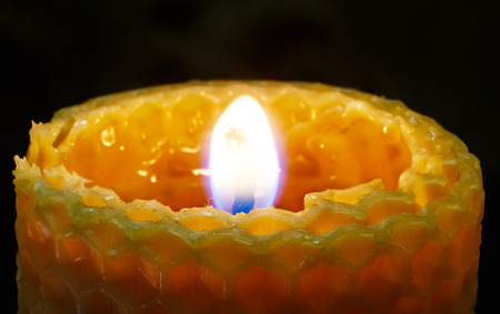 lighted: Lighted honeycomb candle on dark background. Stock Photo