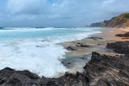 Storm on Castelejo beach with black schist cliffs (Algarve, Portugal).