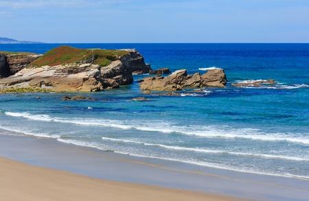 islas: Atlantic sandy Islas beach (Galicia, Spain) with pink flowers on rock.