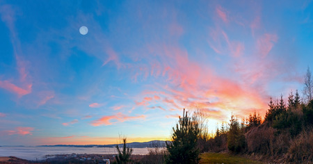 Fantastical sunset scenery with pink clouds in sky and waves of clouds over foothills. Stock Photo