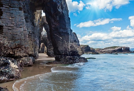Natural rock arches on Cathedrals beach  in low tide (Cantabric coast, Lugo (Galicia), Spain) and sunshine. Stock Photo