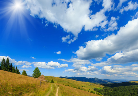 Beautiful blue sunshine sky with white cumulus clouds over summer Carpathian mountain (Ukraine, Verkhovyna district, Ivano-Frankivsk region).