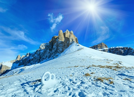 sella: Wedding ring sculpture from the snow on winter mountain sunshiny slope (Sella Pass , Italy).