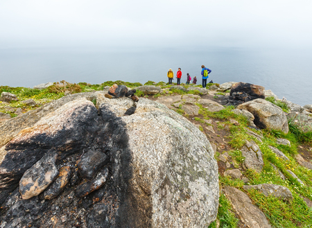 FISTERRA, PORTUGAL -  MAY 14, 2016: Fireplaces on cape Fisterra where in  tradition travelers burned some of their clothes at the end of the way (Galicia, Spain). Summer foggy weather.