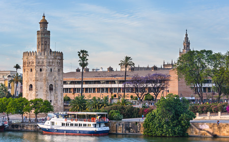 water bus: SEVILLE, SPAIN -  MAY 26, 2016: Evening summer Seville city view with Guadalquivir river embankment and pleasure boat (Spain).