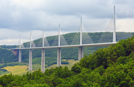 millau: MILLAU, FRANCE -  JUNE 03, 2016: Cable-stayed bridge Millau Viaduct over summer valley River Tarn.