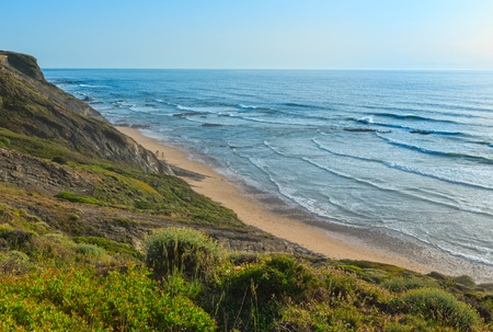 Evening summer ocean view over Carriagem beach at low tide (Aljezur, Algarve, Portugal).
