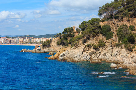 Summer sea rocky coast view with Castle of Sant Joan and Sa Caleta beach, Lloret de Mar town, Spain. People are unrecognized.