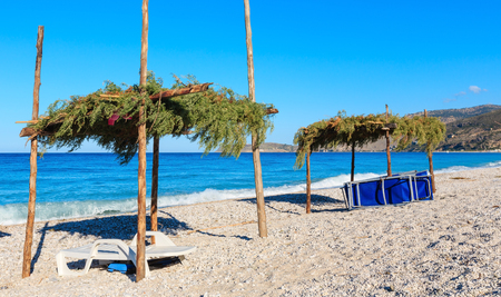 canopies: Summer morning pebbly beach with sunbeds and canopies (Borsh, Albania). Stock Photo