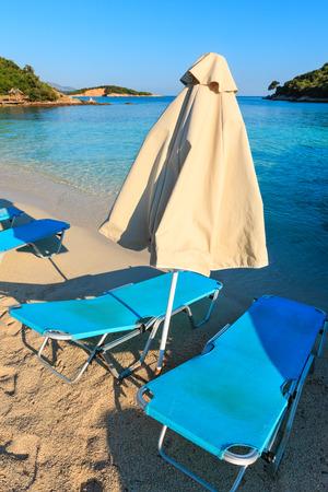 sunshade: Summer morning sandy Ksamil Beach with sunbeds and sunshades (Albania).