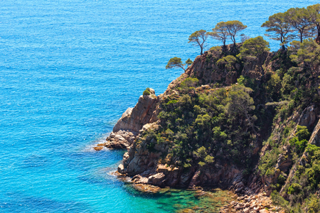 Summer sea rocky coast top view with sunny sparkles on water surface (Spain). Stock Photo