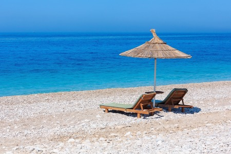 Summer morning sandy beach with sunbeds and strawy sunshade (Albania). Stock Photo