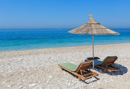 sunshade: Summer morning sandy beach with sunbeds and strawy sunshade (Albania). Stock Photo
