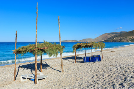 canopies: Summer morning beach with sunbeds and canopies (Borsh, Albania).