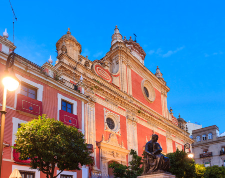 martinez: Red facade of the Church of Saviour (Architects Esteban Garcia and Leonardo de Figueroa, 1674-1712) and Statue of Martinez Montanes (Work of the sculptor Agustin Sanchez Cid., 1924) at Plaza del Salvador in evening, Seville, Spain.