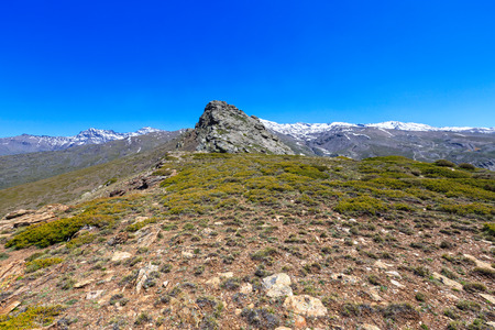 Summer mountain landscape with snow on ridge (Sierra Nevada National Park, near Granada, Spain). Stock Photo
