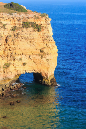 Natural arch in cliff. Summer Atlantic rocky coast view near beach Praia da Afurada (Lagoa, Algarve, Portugal).