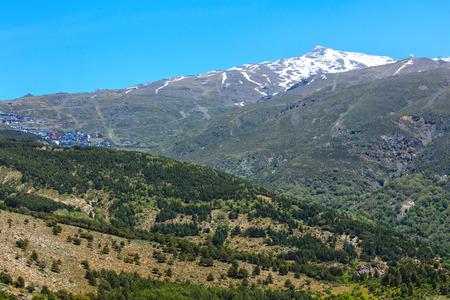 Summer mountain landscape with snow on peak (Sierra Nevada National Park, near Granada, Spain). Stock Photo