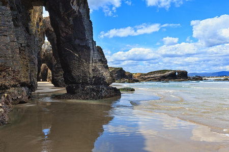 Natuurlijke rotsbogen op kathedralenstrand bij laag tij (Cantabric kust, Lugo (Galicië), Spanje). Volkeren zijn onherkenbaar. Stockfoto