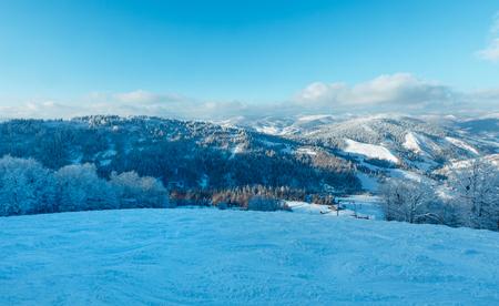 The first shadows of setting sun on winter mountain slopes with surface lift and ski run (Skole Beskids, Lviv Oblast, Carpathians, Ukraine) Stock Photo