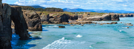 Natural rock arches on As Catedrais beach in low tide (Cantabric coast, Lugo (Galicia), Spain). Peoples are unrecognizable. Two shots stitch high-resolution panorama.