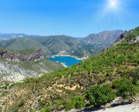 Blue lake in Sierra Nevada National Park, near Granada, Spain. Summer mountain sunshiny landscape.