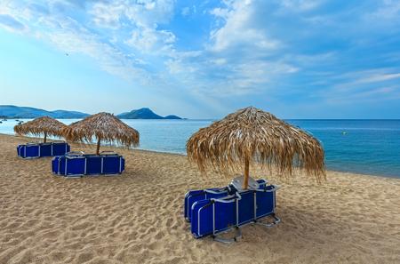 Summer morning sandy Tristinika beach with sunbeds and sunshades (Sithonia, Chalkidiki, Greece). Stock Photo