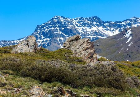 夏の山の風景 (シエラネバダ国立公園、グラナダ、スペインの近く) の斜面に雪。