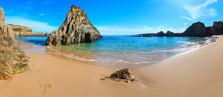 Summer sandy Mexota beach and pointed rock near (Spain). Atlantic Ocean coastline landscape. Three shots stitch image.