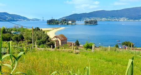 Sandy beach in Cesantes town and San Simon island (Galicia, Spain). Summer Ria de Vigo landscape. Stock Photo