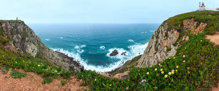 declaring: Summer blossoming Cape Roca (Portugal) with lighthouse and monument (on left) declaring Cabo da Roca as the westernmost extent of continental Europe. People are unrecognizable. Five shots stitch high-resolution panorama. Stock Photo