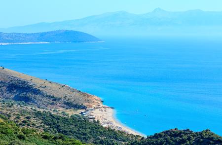 Adriatic sea summer coast with beach and Corfu island in mist (Lukove komuna, Albania). View from mountain pass.