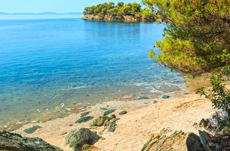 Morning summer Aegean Sea coast landscape with pine trees on shore and beach, Sithonia (near Ag. Kiriaki), Halkidiki, Greece.