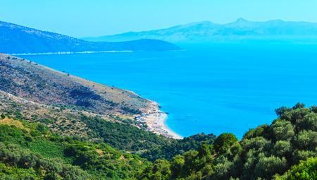 Adriatic sea summer coast with beach and Corfu island in mist(Lukove komuna, Albania). View from mountain pass.