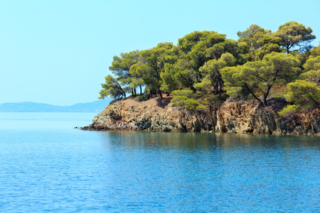 Morning summer Aegean Sea rocky coast landscape with pine trees on shore, Sithonia (near Ag. Kiriaki), Halkidiki, Greece. Stock Photo