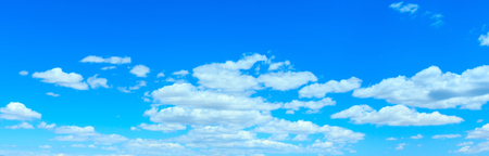 White fluffy clouds in the blue azure sky panorama. Summer good weather background.